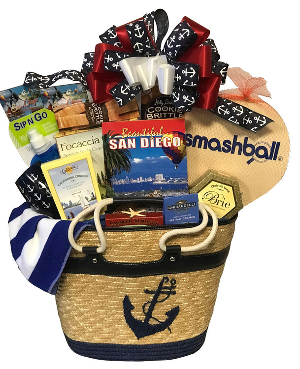"This gorgeous over sized, high end, designer tote bag makes for a striking nautical presentation. This is a perfect raffle prize for a nautical themed event (when you want to make a really big splash! , a huge               "" Welcome To San Diego!,""  or a special housewarming gift for someone who just got their dream home by the ocean! The tote bag can be used as a magazine basket in the home, or used for picnics, day at the beach or boating. Includes a towel, sip and go water bottle, Beautiful San Diego (book), paddle ball game, California Crunch snack mix, cheese, crackers, assorted cookies and confections, California almonds, an unbreakable stemless wine glass with anchor design and more."