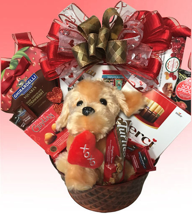 Our adorable plush puppy really steals the show and delivers a big smile. He is nestled among decadent chocolates and confections, including a heart shaped box of dark chocolate & strawberry Ghirardelli Chocolates, Guylian Chocolates, Chocolate Turtles, gourmet assorted mini chocolate bars by Merci , Bog Frogs, gourmet popcorn and more. The elegant designer tin make a great fruit bowl, planter, or home accent.