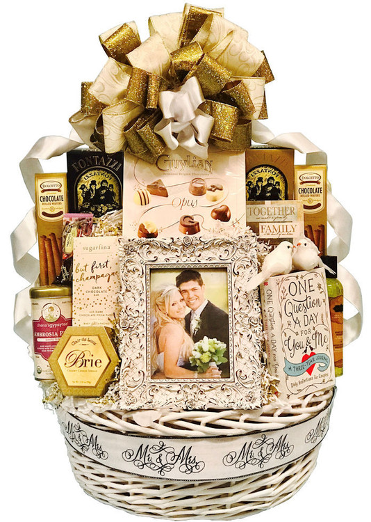 "A stunning presentation and memory making assortment for the newlyweds! Includes a fancy, designer wedding frame, A book they will write together and cherish forever called ""One Question A Day"", a candle, massage lotion, cheese, crackers, tea, cookies, gourmet sweet and savory pretzels, fine chocolate assortment,  a champagne chocolate bar, and two doves as an enhancement in a white basket.  Items of equal or greater value may be substituted depending on availability."