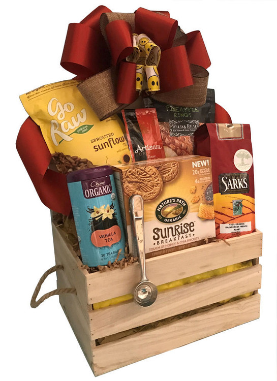 A wooden crate filled with an assortment of  organic coffee, tea, breakfast biscuits, dried fruits and seeds. Also includes a cool coffee scoop that doubles as a coffee bag sealer to keep the coffee fresh.