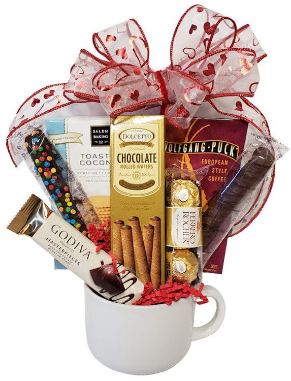 An over sized mug filled with coffee, chocolates, double dipped chocolate pretzel rods, Ferrero Rocher, Godiva chocolate, delicious toasted coconut cookies and chocolate filled rolled pastry cookies. The mug can be used for coffee or tea, soup, ice cream, cereal or snacks!