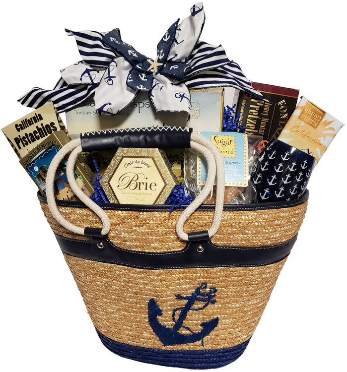 This high end, fully lined, resort tote bag has an inside zippered pocket and a rope handle. It can be enjoyed for a weekend getaway, day at the beach, picnics, boating and more. Includes: A stemless anchor wine glass, honey mustard pretzels, chocolate, cheese, crackers, home made sea salt caramels, smoked almonds, pistachios, and cookies. This is also a popular raffle prize.  Items of equal or greater value may be substituted depending on availability and the discovery of great new seasonal items. Chocolate is substituted when item is being shipped during hot months.