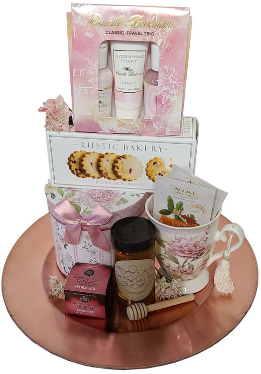 A pretty pink platter with a beautiful porcelain cup, matching floral gift box, with cookies,  tea, honey, honey dipper, shortbread cookies, and a chocolate truffle.