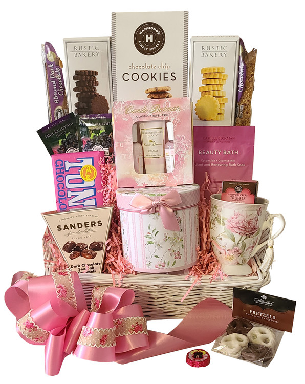 Lovely basket with a little bit of everything. Includes a beautiful porcelain mug and matching gift box keepsake, yummy chocolates, biscotti, cookies and shortbread, A Camille Beckman Spa Set, Bath Soak, and assorted teas. All elegantly presented in a white tray basket with ear handles, and topped off with a pretty, hand made bow.