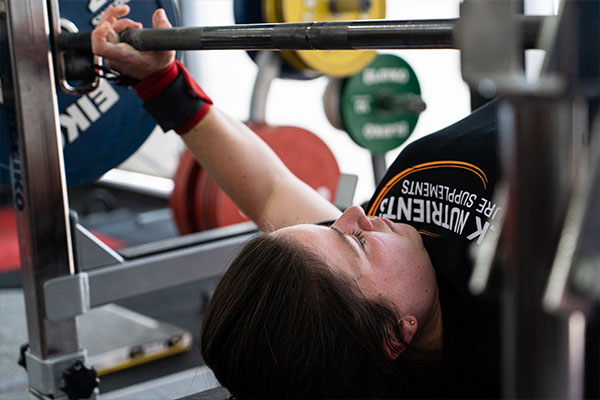 Training for powerlifting involves increasing strength and improving form of the big three lifts through a combination of compound and accessory movements.