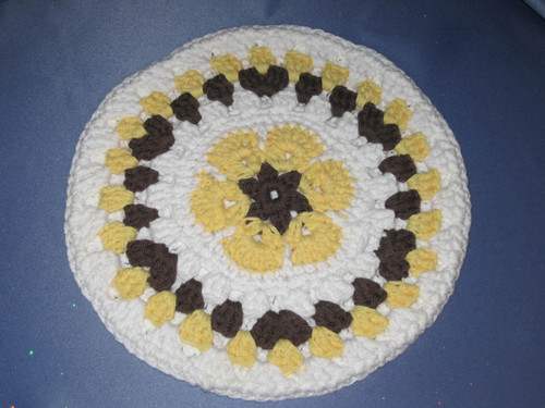 Round African Flower Potholder-Trivet in Yellow and Brown.