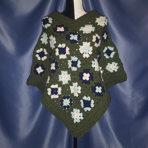 Granny Square Poncho in Dark Blue Pale Green and White surrounded by Dark Green by Mumsie of Stratford.