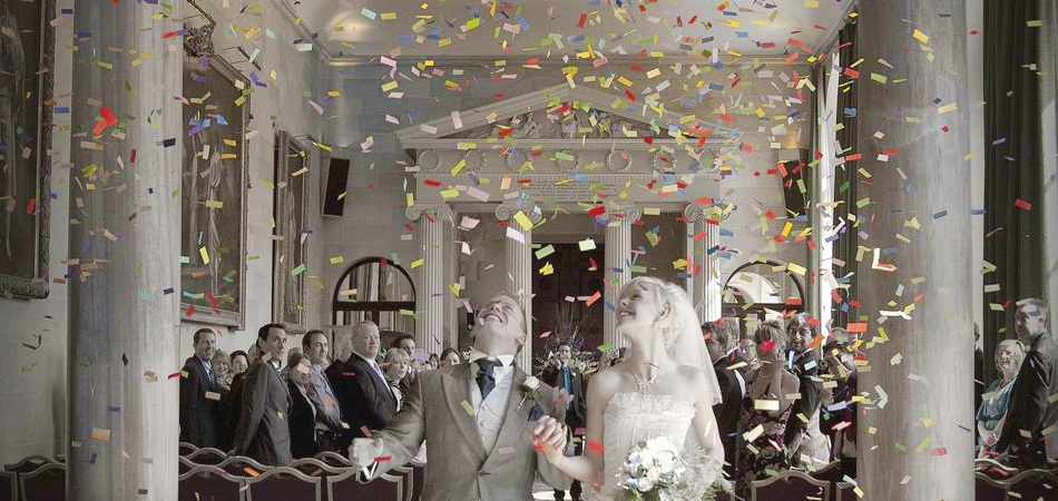 Bride and groom walking through falling confetti