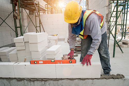 Man on a building site laying blocks with a level