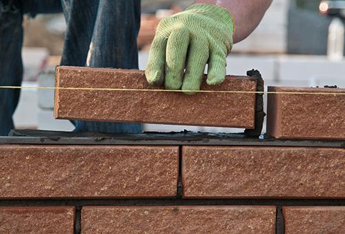 Closeup of a worker laying bricks | SafetyDocs