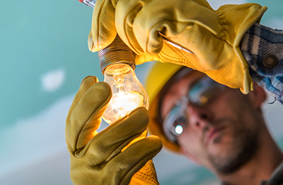 Close up image of an electrician changing a lightbulb