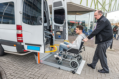 Personal carer helping man in a wheelchair into a van SafetyDocs