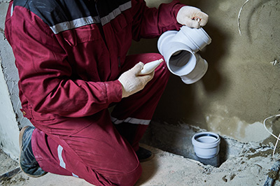 Plumber in overalls installing new sewerage pipe|SafetyDocs