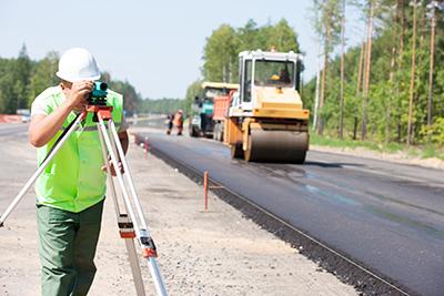 Surveyor on roadworks with asphalt being laid in the background|SafetyDocs