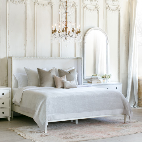 Eloquence® Cassia Antique Reproduction Bed in Ivory Velvet and Antique White With Gold Leaf Finish in a French Style Bedroom  with Chandelier