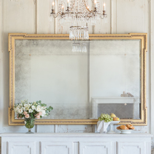Eloquence® Rodin Mirror in Distressed Gold Finish Hanging Horizontally in a Living Room with Chandelier, Cabinet, and a Pair of Counter Stools Close View