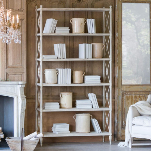 Eloquence® Tresor Bookshelf in Provencal White Finish in French-style Living Room with Fireplace and Decorative Books and Jars