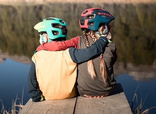 Kids sitting down hugging wearing their Scott Cycling Helmet