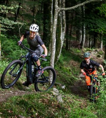 Woman and a Man mountain biking on their Scott's Mountain Electric Bikes