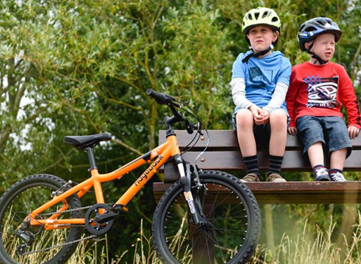 Kids sitting on a bench beside their Ridgeback bike