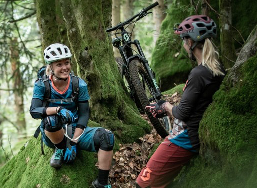 2 women having a rest while riding their Scott's mtb in a forest