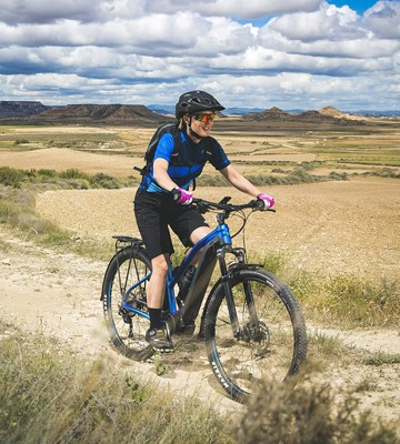 Woman on an ebike on a trail with the mountains in the background