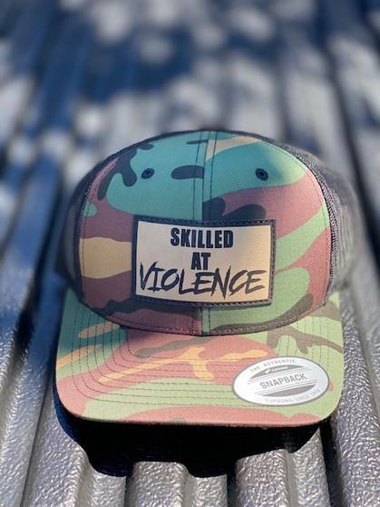 SKILLED AT VIOLENCE TRUCKER HAT (M81 Woodland)