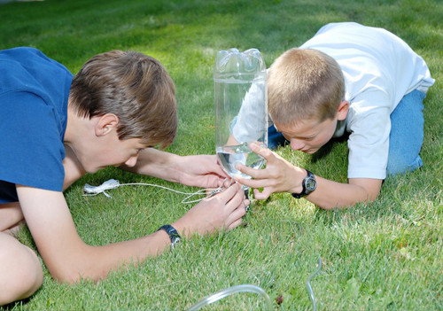 two boys set up water rocket launcher in grass