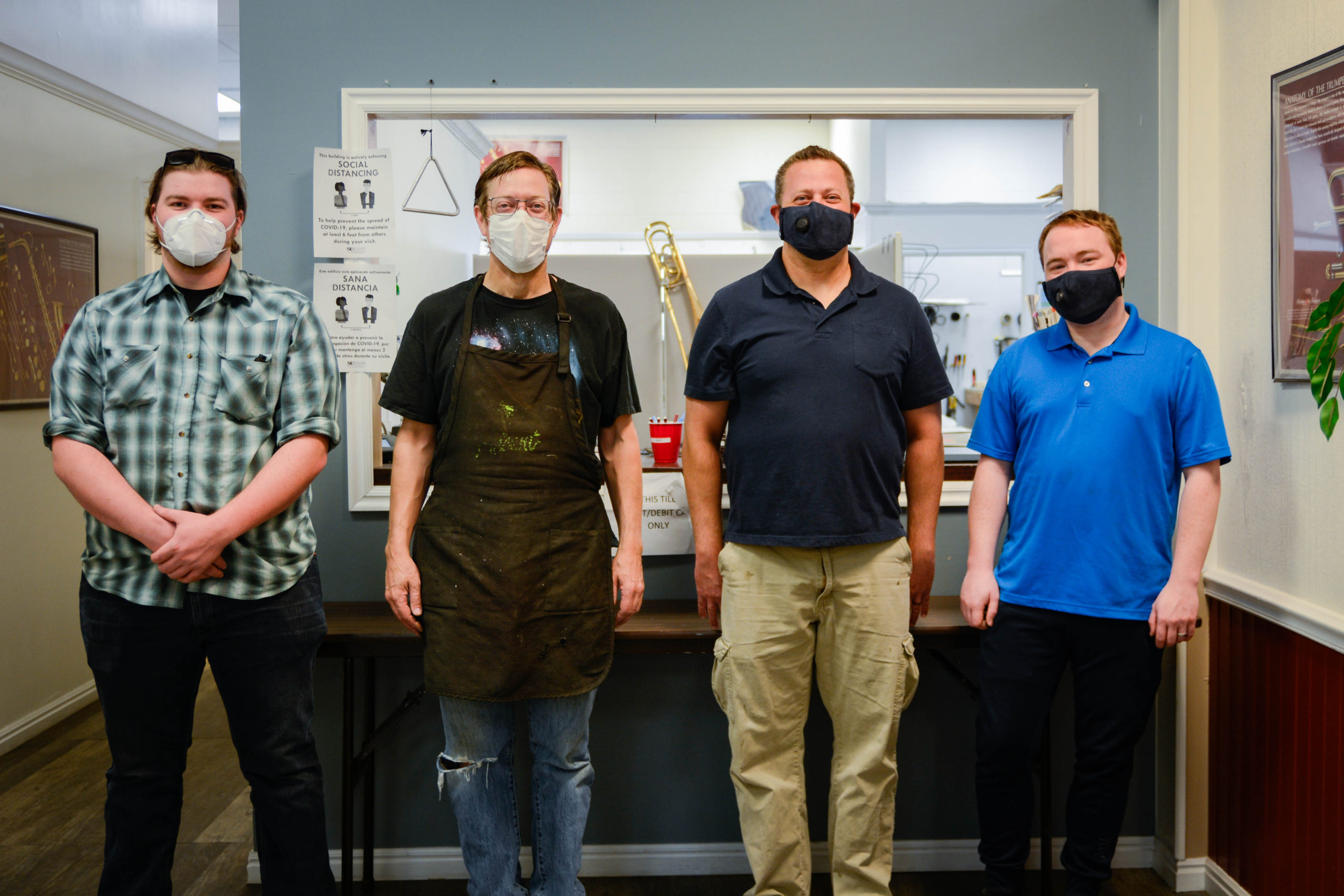 Band repair technicians Maxwell Wasson, James Bauer, Dan Hansen, and Tyler Olsen standing in front of the Murray band repair window wearing Covid masks.