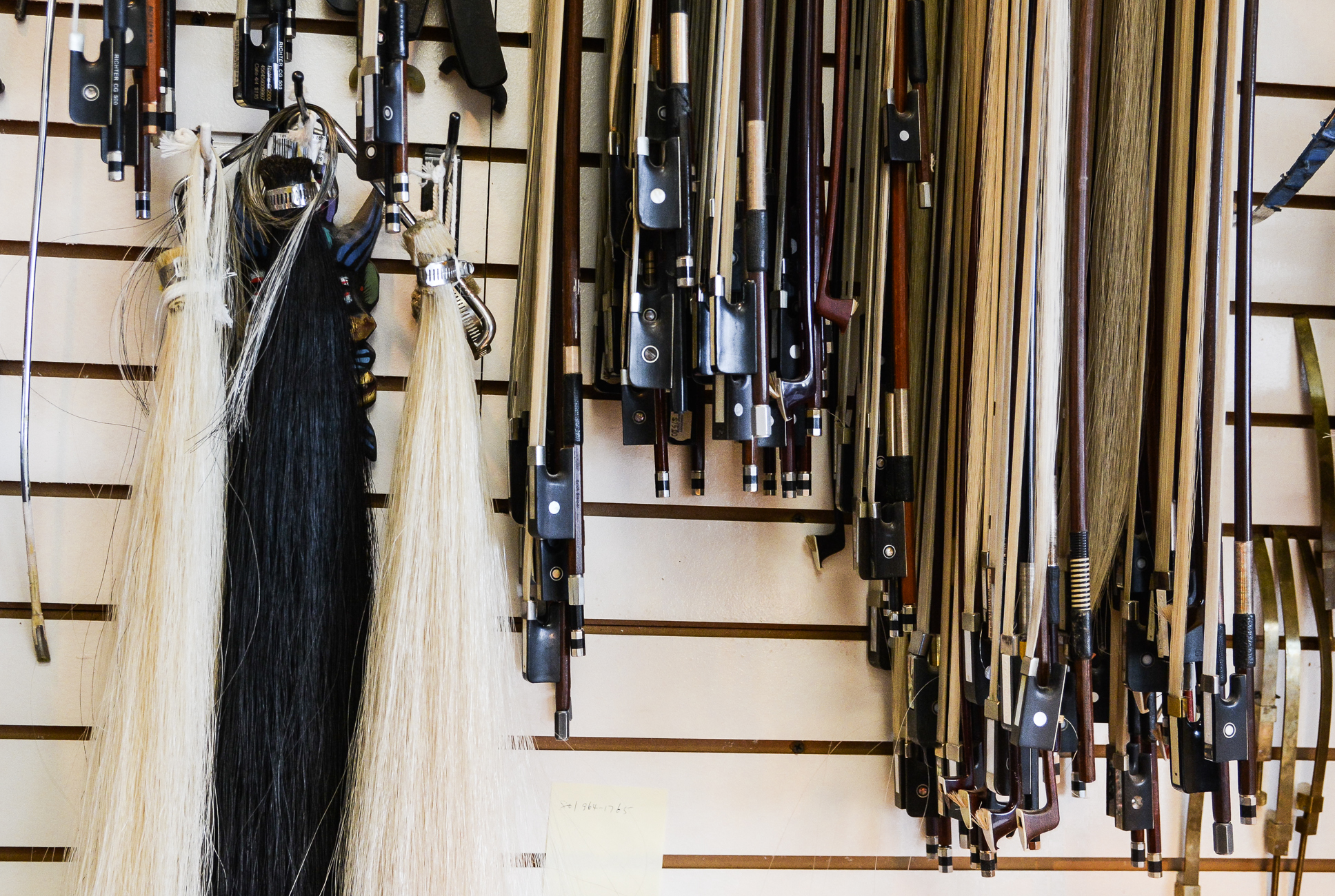 a wall with hanging Mongolian and Siberian horsehair next to dozens of violin, viola, cello and bass bows.