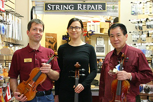 Three string repair technicians standing in front of the Murray location string repair window.
