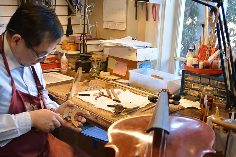 a string repair tech working on a cello bridge