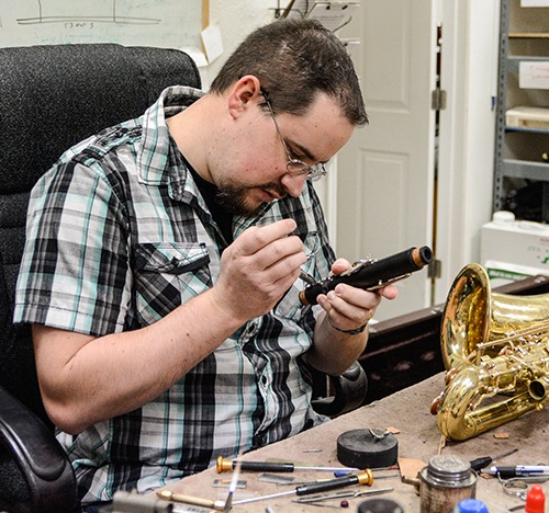 Band repair technician working on a clarinet.