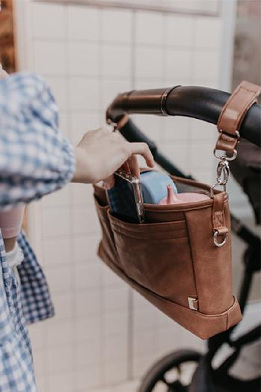 OiOi Faux Leather Stroller Organiser at Baby Barn Discounts OiOi spacious pram caddy has configurable compartments and comes with a complimentary crossbody strap.