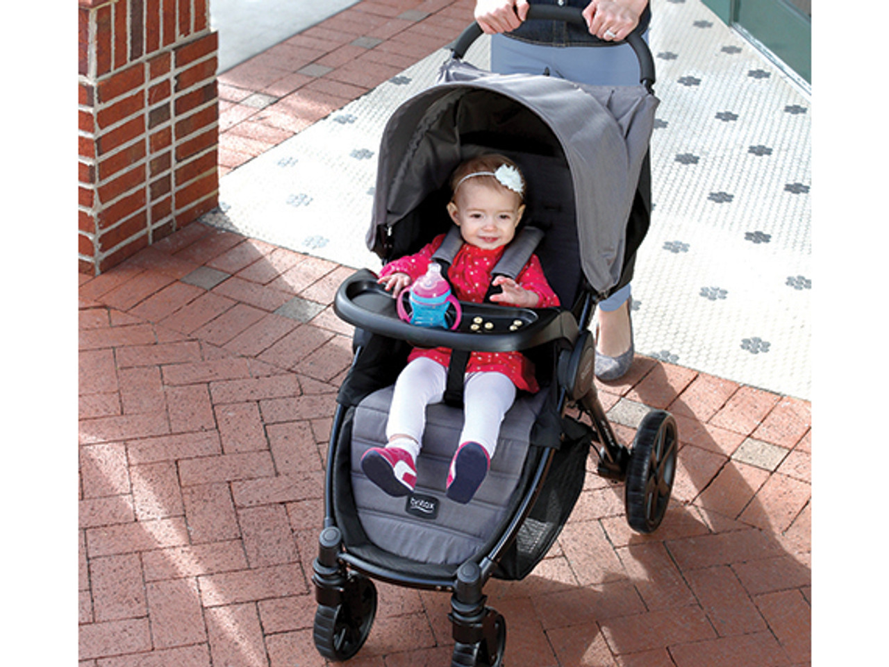 The Britax Agile Child Tray easily attaches to the stroller frame and features a designated child drink holder and a flat surface for snacks or other items.