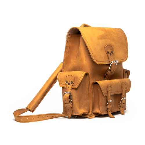 This is a tan brown leather backpack with three pockets on the outside. The image of this backpack is the front side.