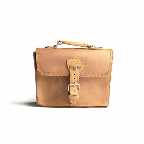 This is the front side of a tan brown leather satchel with a front pocket not angled.