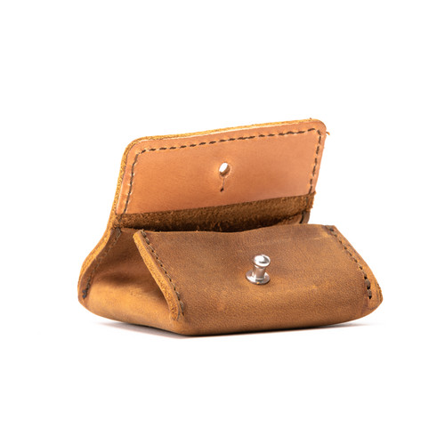 This is a tan brown leather coin purse open.