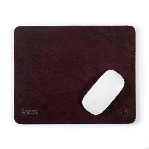 This is a reddish brown leather normal mouse pad with a mouse on it.
