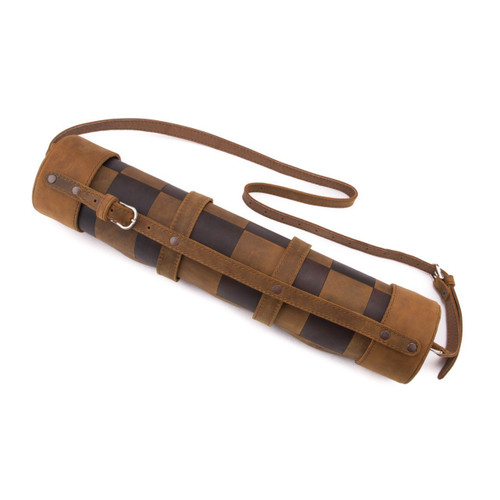 This is a leather travel chess set that is rolled up with a shoulder strap.
