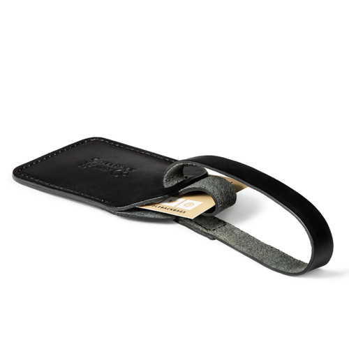 This is a black leather luggage tag made of vegetable tanned leather laying down.