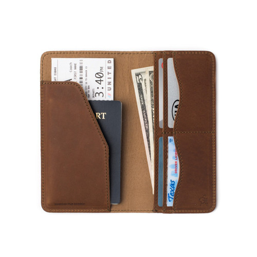 This is a long tall interior picture tan brown leather wallet with a passport and cards.