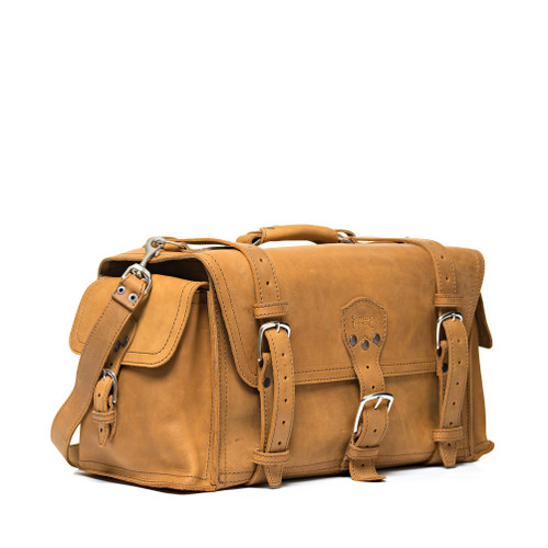 This tan brown leather duffle bag is side front facing and has pockets on the sides for overnight trips.