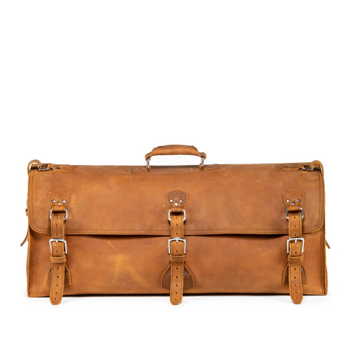 This leather duffle bag is tan brown and has three straps on it. It is showing the front side.