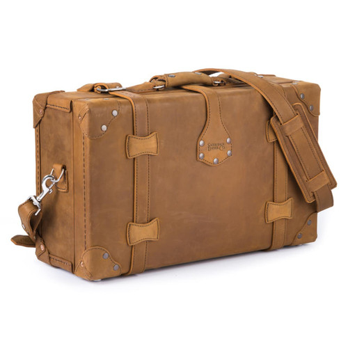 This is a tan brown leather carry on luggage that is showing the side.
