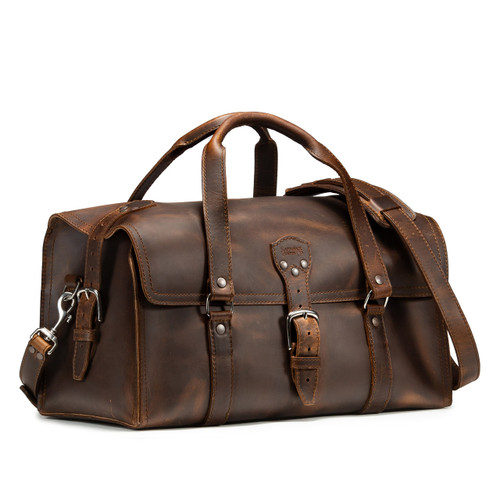 This is a dark brown leather duffle bag that has three straps to close it and has two round handles from the front side.