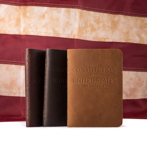 Desk size Constitution of the United States for the pocket. This picture has three in different colors in front of an American flag.