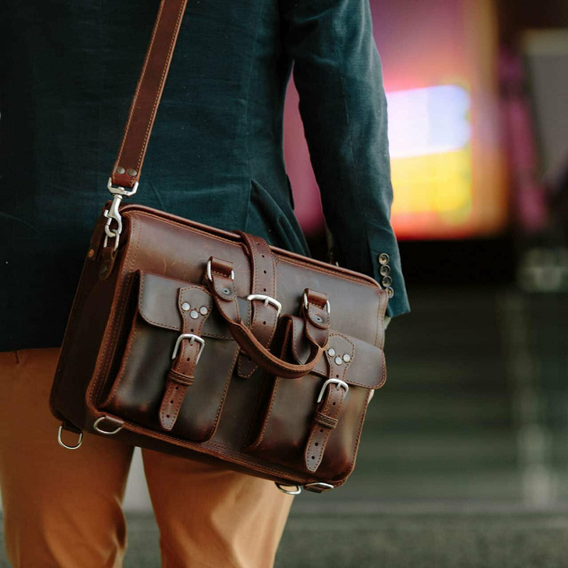 This is a red brown leather briefcase hanging on someone's shoulder.