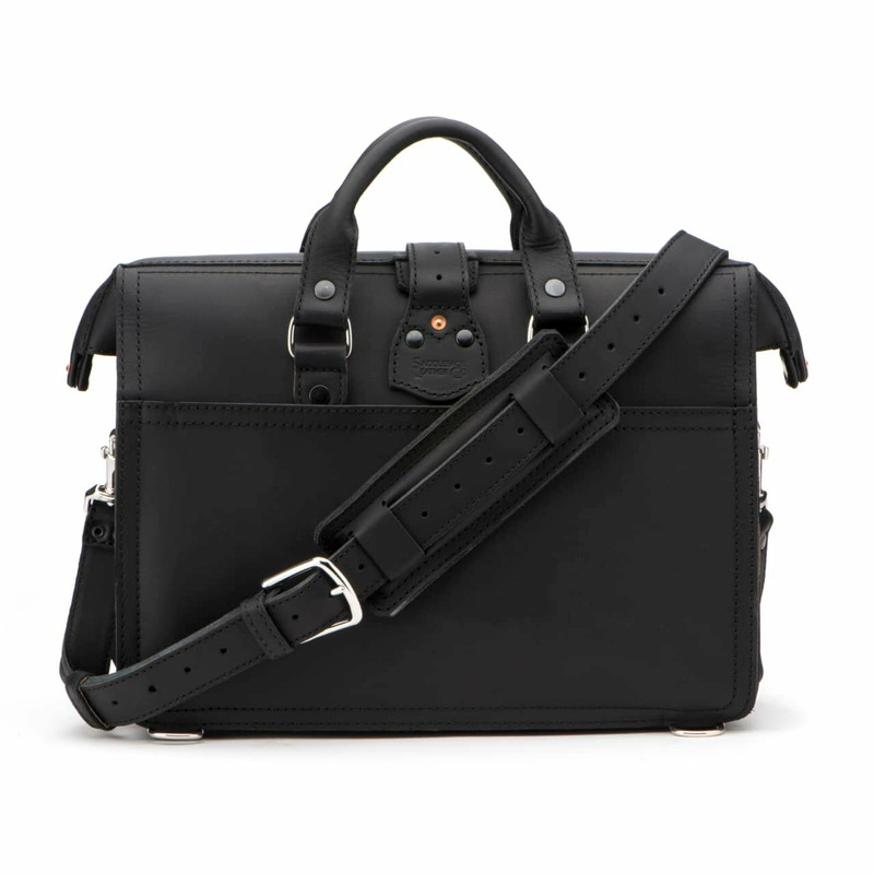 The black leather briefcase is facing backwards with the strap behind its back..