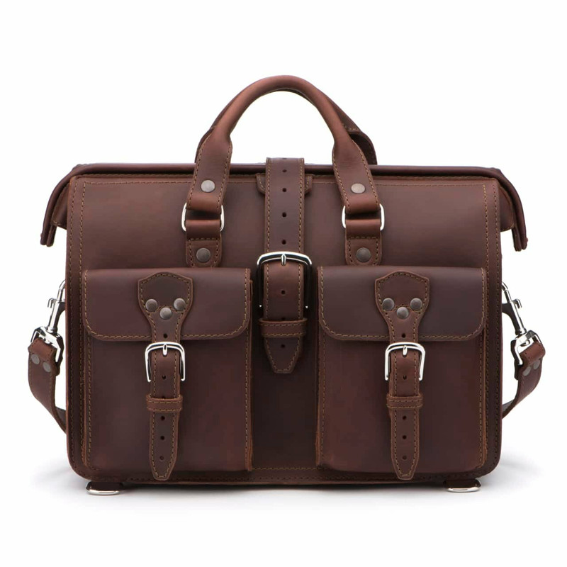 This red brown leather briefcase is staring straight into the camera and has a triangle design for the buckles.